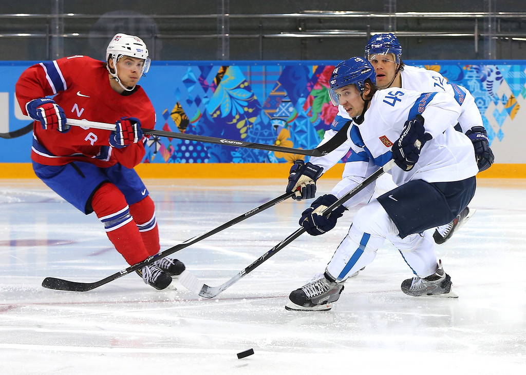 . Mats Rosseli Olsen #51 of Norway and Sami Vatanen #45 of Finland go for a loose puck in the second period during the Men\'s Ice Hockey Preliminary Round Group B game on day seven of the Sochi 2014 Winter Olympics at Shayba Arena on February 14, 2014 in Sochi, Russia.  (Photo by Martin Rose/Getty Images)