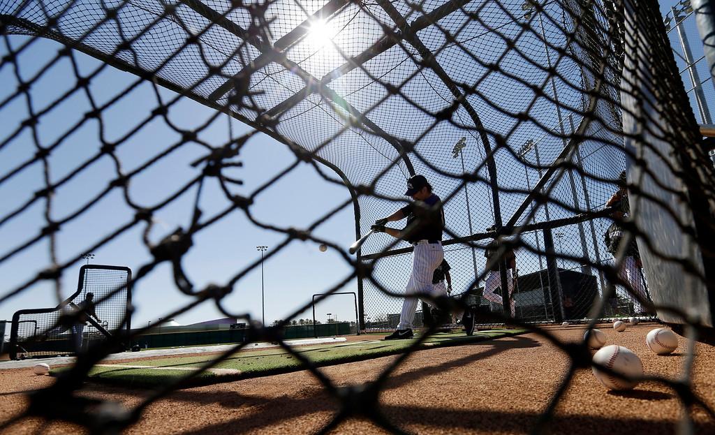 . Colorado Rockies\' Todd Helton takes batting practice during a spring training baseball workout Sunday, Feb. 17, 2013, in Scottsdale, Ariz. (AP Photo/Darron Cummings)