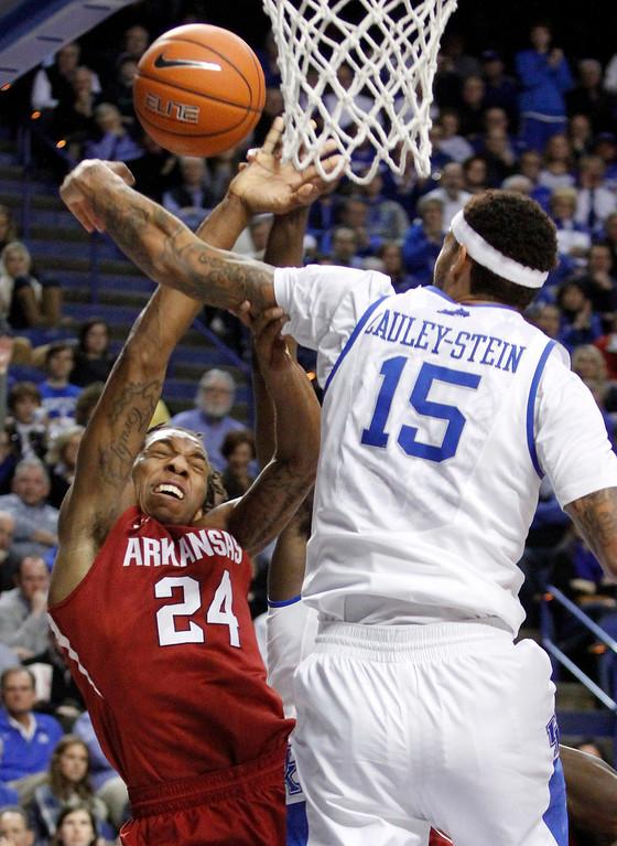 . Arkansas\' Michael Qualls (24) has his shot pressured by Kentucky\'s Willie Cauley-Stein (15) during the second half of an NCAA college basketball game, Thursday, Feb. 27, 2014, in Lexington, Ky. Arkansas won 71-67. (AP Photo/James Crisp)