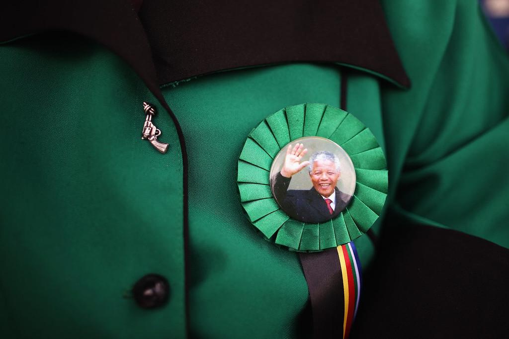 . A woman wears a pin badge depicting an image of Nelson Mandela during the funeral service of the former South African President Nelson Mandela during his state funeral on December 15, 2013 in Qunu, South Africa. Mr. Mandela passed away on the evening of December 5, 2013 at his home in Houghton at the age of 95. Mandela became South Africa\'s first black president in 1994 after spending 27 years in jail for his activism against apartheid in a racially-divided South Africa.  (Photo by Dan Kitwood/Getty Images)