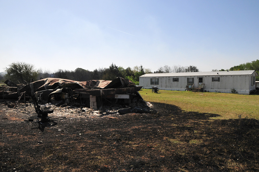 . The charred remains of a trailer home sit in front of a home that narrowly avoided the flames after a wildfire tore through the area Sunday on Monday May 5, 2014 in Guthrie, Oklahoma. (AP Photo/Nick Oxford)