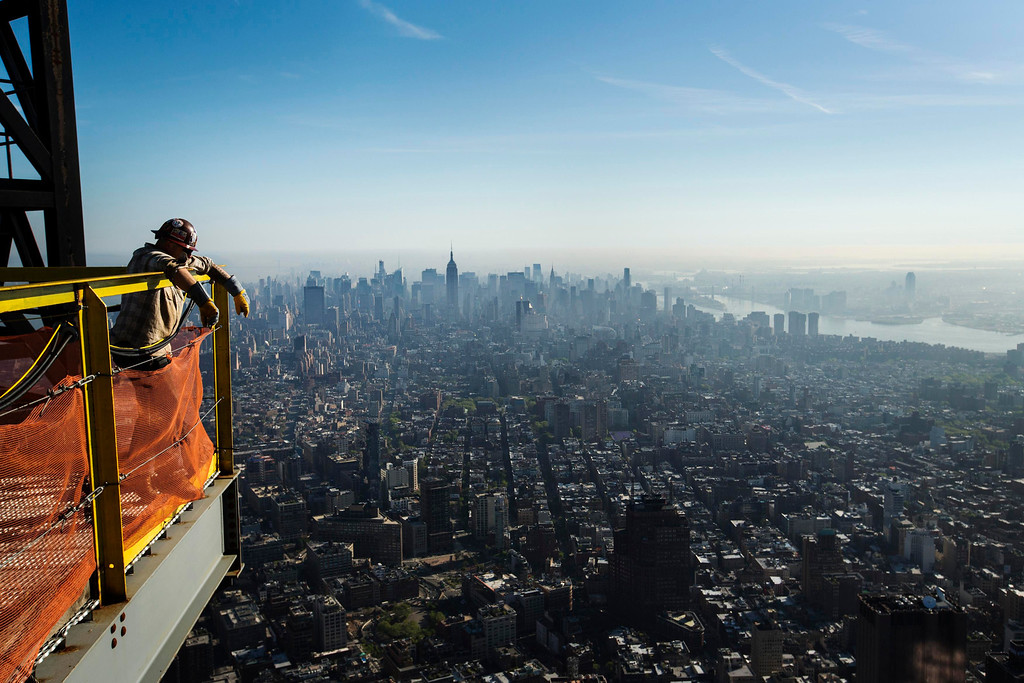. An iron worker leans on a safety fence to look at the New York skyline after watching a crane lift the final piece of the spire to the top of the One World Trade Center in New York May 10, 2013. Workers cheered and whistled as they completed the spire on New York\'s One World Trade Center on Friday, raising the building to its full height of 1,776 feet and helping fill a void in the skyline left by the September 11, 2001 attacks. REUTERS/Lucas Jackson