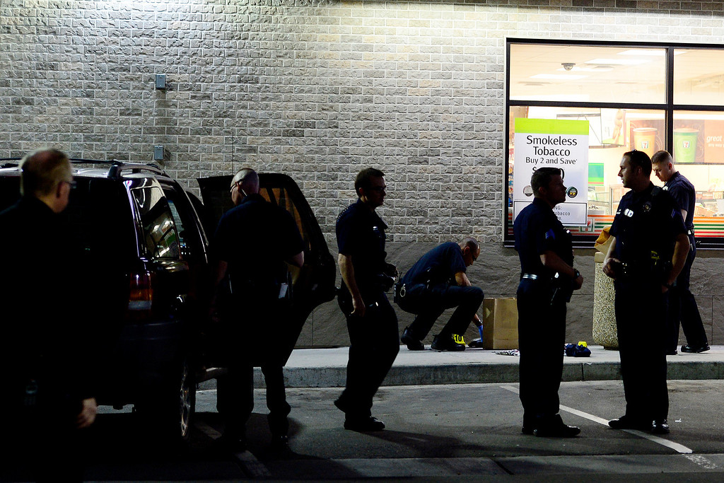 . DENVER, CO - APRIL 29: Officers investigate an SUV at 7-Eleven near 6th and Federal Boulevard after a boy was shot nearby and taken to the convenience store. The child who was shot was reported to be in critical condition. (Photo by AAron Ontiveroz/The Denver Post)