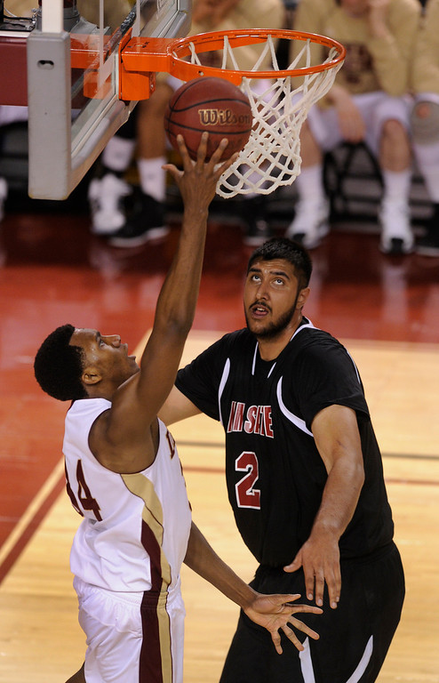 . DENVER, CO. - MARCH 2: Pioneers forward Chris Udofia (34) cut around Aggies defender Sim Bhullar (2) for a way to the basket in the second half. The University of Denver men\'s basketball team defeated New Mexico State 66-60 Saturday evening, March 2, 2013 at Magness Arena. (Photo By Karl Gehring/The Denver Post)