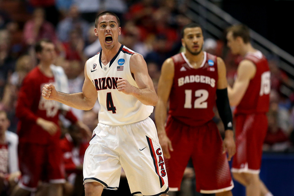 . T.J. McConnell #4 of the Arizona Wildcats celebrates in the second half in front of Traevon Jackson #12 of the Wisconsin Badgers during the West Regional Final of the 2014 NCAA Men\'s Basketball Tournament at the Honda Center on March 29, 2014 in Anaheim, California.  (Photo by Jeff Gross/Getty Images)