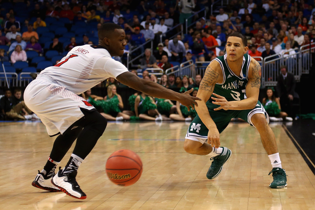 . Michael Alvarado #31 of the Manhattan Jaspers passes the ball against Chris Jones #3 of the Louisville Cardinals during the second round of the 2014 NCAA Men\'s Basketball Tournament at Amway Center on March 20, 2014 in Orlando, Florida.  (Photo by Mike Ehrmann/Getty Images)
