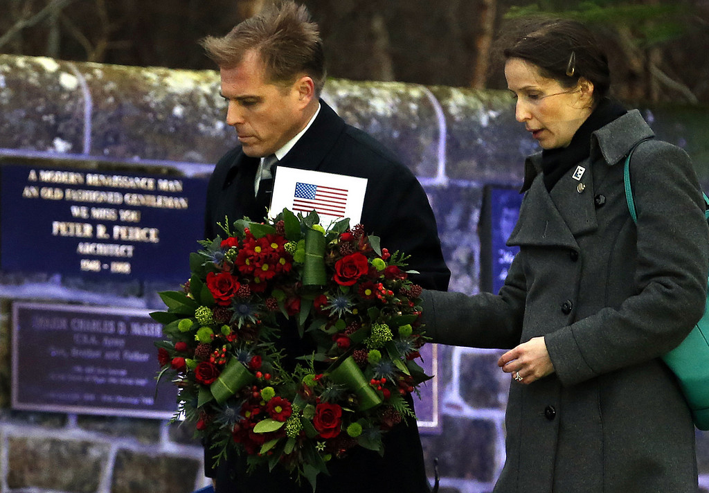 . Craig Lynes, left, US government representative and Zoja Bazarnic, right, U.S consulate principal officer carry a wreath to the main memorial stone in memory of the victims of the Lockerbie Pan Am flight 103 bombing in the garden of remembrance at Dryfesdale Cemetery, near Lockerbie, Scotland. Saturday Dec. 21, 2013. (AP Photo/Scott Heppell)