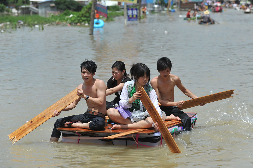 . Residents make their way through floodwaters on a makeshift raft in the Chaonan district of Shantou, in southern China\'s Guangdong province on August 19, 2013.  Devastating floods at opposite ends of China have left 105 people dead and another 115 missing in recent days, state media said.   AFP PHOTOSTR/AFP/Getty Images
