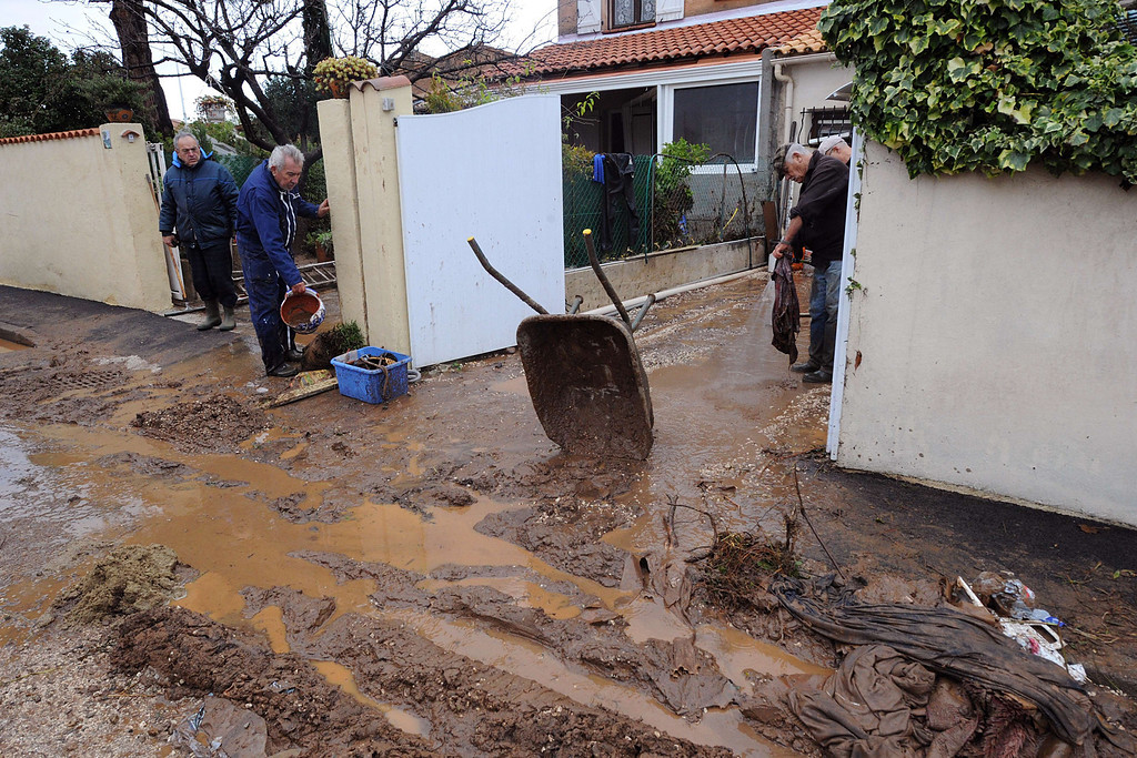 """. Pepole clean their houses on Januray 20, 2014 in La Londe-les-Maures, southeastern France. River levels were receding early today in southeastern France after \""""historic\"""" floods left two people dead and more than 150 were airlifted to safety. A third man disappeared while out on his boat and 4,000 homes have been left without power after the deluge in the department of Var, they said. Local official Laurent Cayrel said one of the victims, a 73-year-old man, died in his basement, while the other was swept away in his car.  BORIS HORVAT/AFP/Getty Images"""