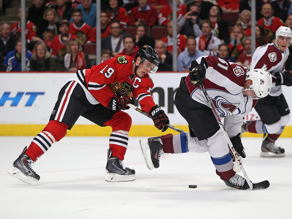 . Jonathan Toews #19 of the Chicago Blackhawks hooks Andre Benoit #61 of the Colorado Avalanche for a penalty in overtime at the United Center on January 14, 2014  in Chicago, Illinois. The Avalanche defeated the Blackhawks 3-2 in overtime.(Photo by Jonathan Daniel/Getty Images)