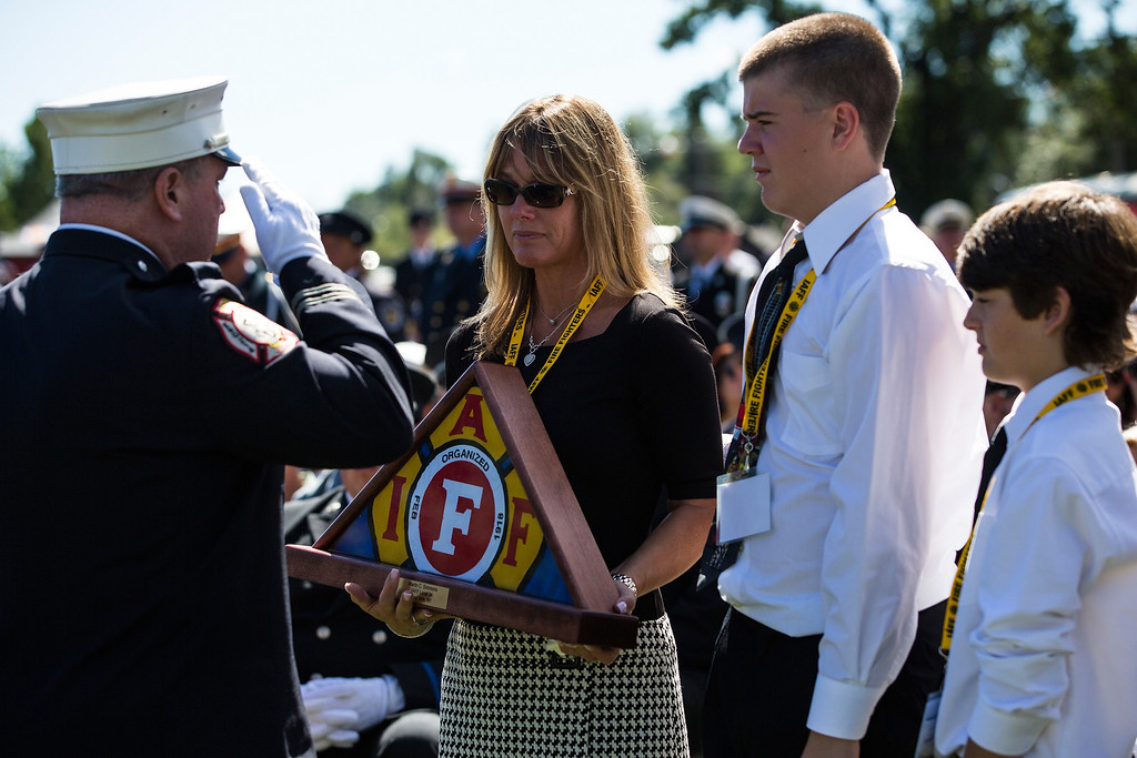 . Judi Simmons along with her sons, Kevin,15, and Ryan, 13, are presented a IAFF flag for her late husband, Martin, during the annual IAFF Fallen Fire Fighter Memorial at Memorial Park in Colorado Springs, Colorado on Saturday, Sept. 21, 2013.(AP Photo/The Gazette, Kent Nishimura)