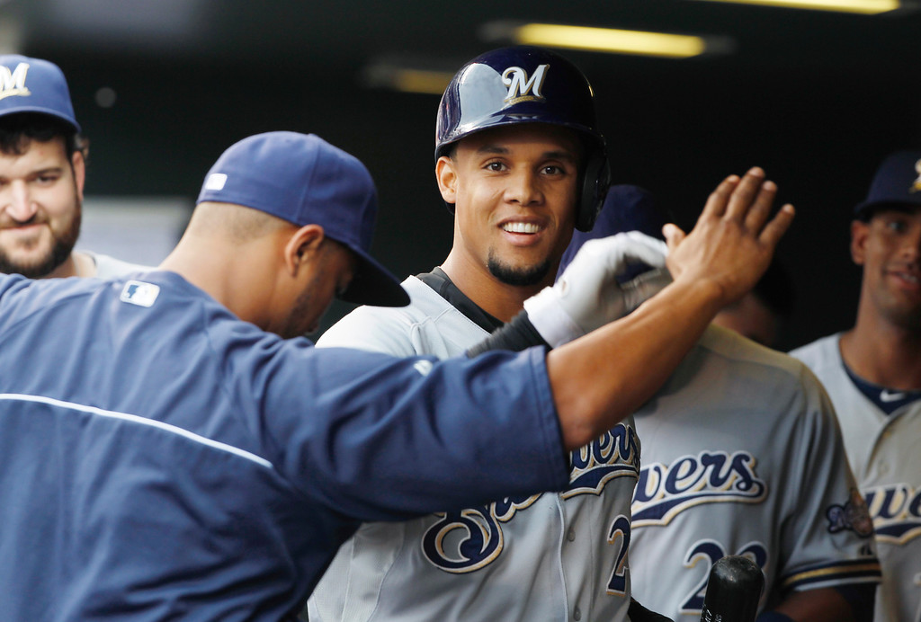 . Milwaukee Brewers\' Carlos Gomez, center, is congratulated after driving in a run with a sacrifice fly against the Colorado Rockies in the first inning of a baseball game in Denver on Saturday, July 27, 2013. (AP Photo/David Zalubowski)