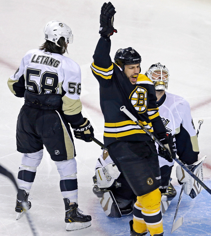 . Boston Bruins left wing Milan Lucic (17) raises his hand as he celebrates a goal by David Krejci during the first period against the Pittsburgh Penguins in Game 3 of the NHL hockey Stanley Cup playoffs Eastern Conference finals, in Boston on Wednesday, June 5, 2013. Penguins defenseman Kris Letang (58) and goalie Tomas Vokoun are behind Lucic. (AP Photo/Charles Krupa)