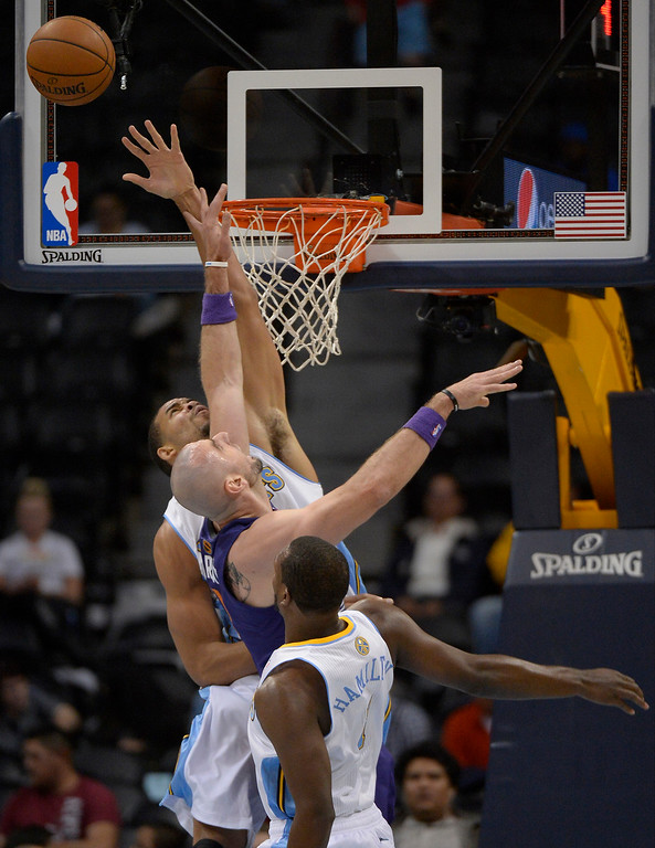 . Phoenix Suns center Marcin Gortat (4) reaches for a rebound with Denver Nuggets center JaVale McGee (34) during the first quarter October 23, 2013 at Pepsi Center. (Photo By John Leyba/The Denver Post)