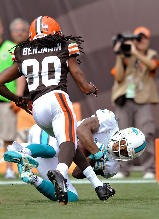 . Miami Dolphins cornerback Nolan Carroll, right, intercepts a pass intended for Cleveland Browns wide receiver Travis Benjamin (80) in the first quarter of an NFL football game Sunday, Sept. 8, 2013, in Cleveland. (AP Photo/David Richard)
