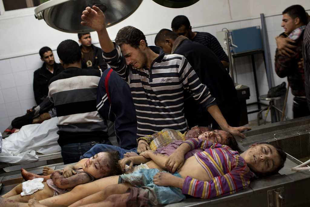 . In this Nov. 18, 2012 file photo, a Palestinian man cries next the dead bodies of four children in the morgue of Shifa Hospital in Gaza City. This photo was one in a series of images by Associated Press photographer Bernat Armangue that won the first place prize in the World Press Photo 2013 photo contest for the Spot News series category. (AP Photo/Bernat Armangue, File)