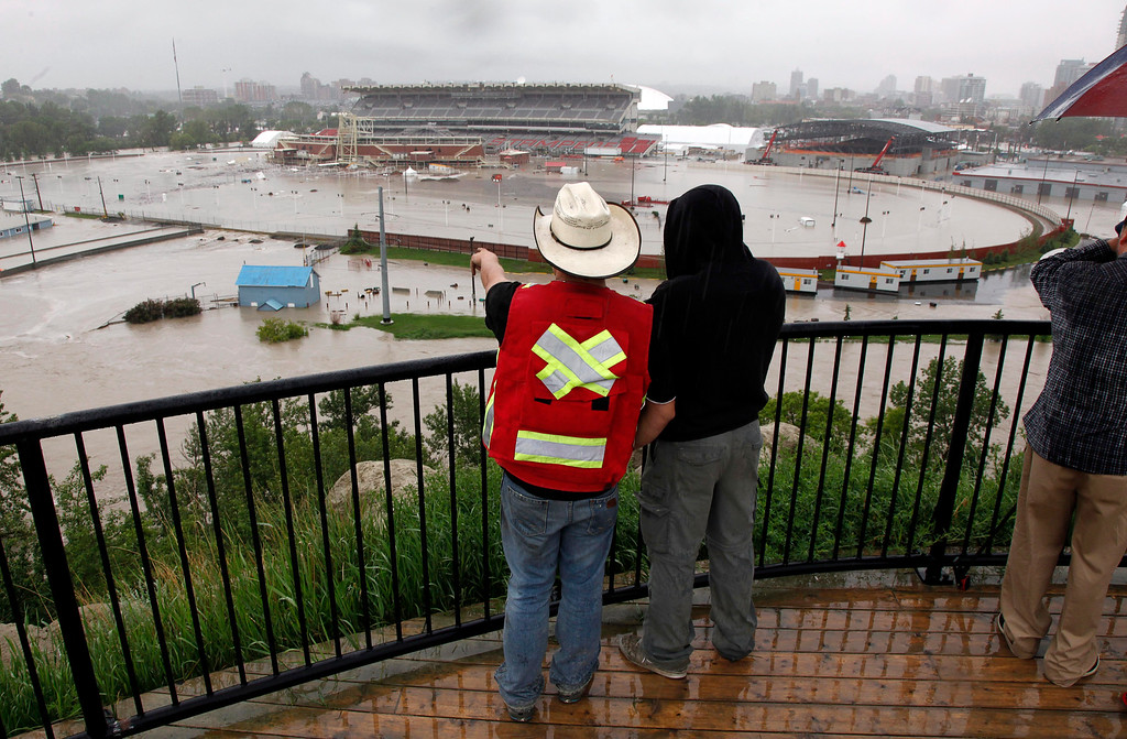 . Calgarians look out over a flooded Calgary Stampede grounds and Saddledome in Calgary, Alberta, Friday, June 21, 2013. Officials estimated 75,000 people have been displaced in the western Canadian city. (AP Photo/The Canadian Press, Jeff McIntosh)