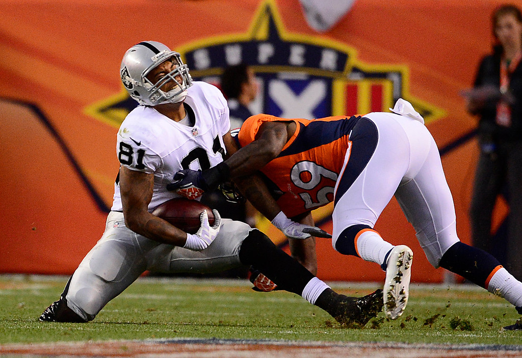 . Denver Broncos linebacker Danny Trevathan (59) makes a tackle on Oakland Raiders tight end Mychal Rivera (81) in the first quarter. The Denver Broncos took on the Oakland Raiders at Sports Authority Field at Mile High in Denver on September 23, 2013. (Photo by AAron Ontiveroz/The Denver Post)