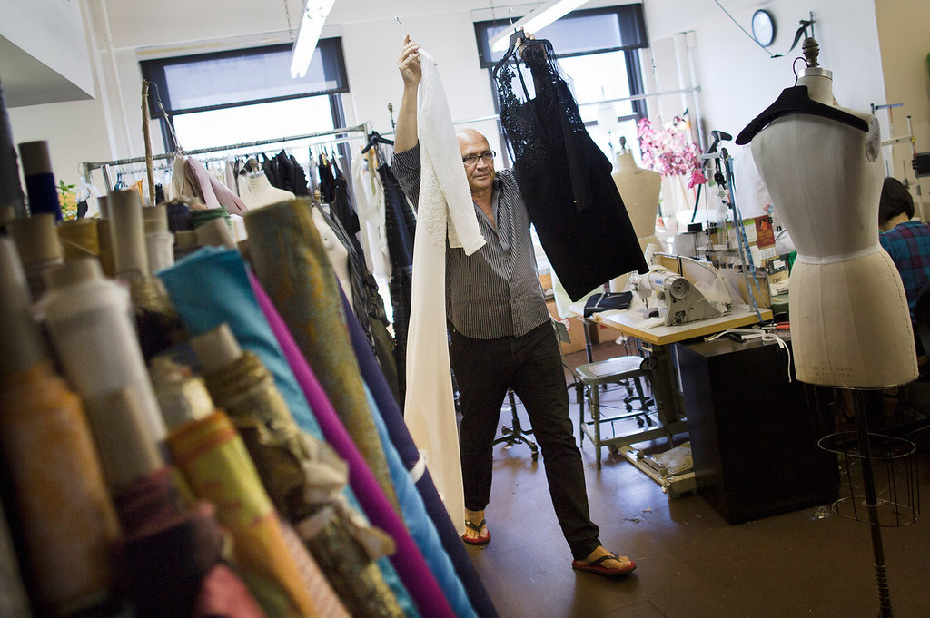 """. Fashion designer Carmen Marc Valvo carries dresses while putting together his Spring 2014 collection, in his studio in New York. Valvo says \""""the most rewarding part of building the collection is when you make your final edit and the run of show is set in stone and no more changes can be made.\"""" (AP Photo/John Minchillo)"""