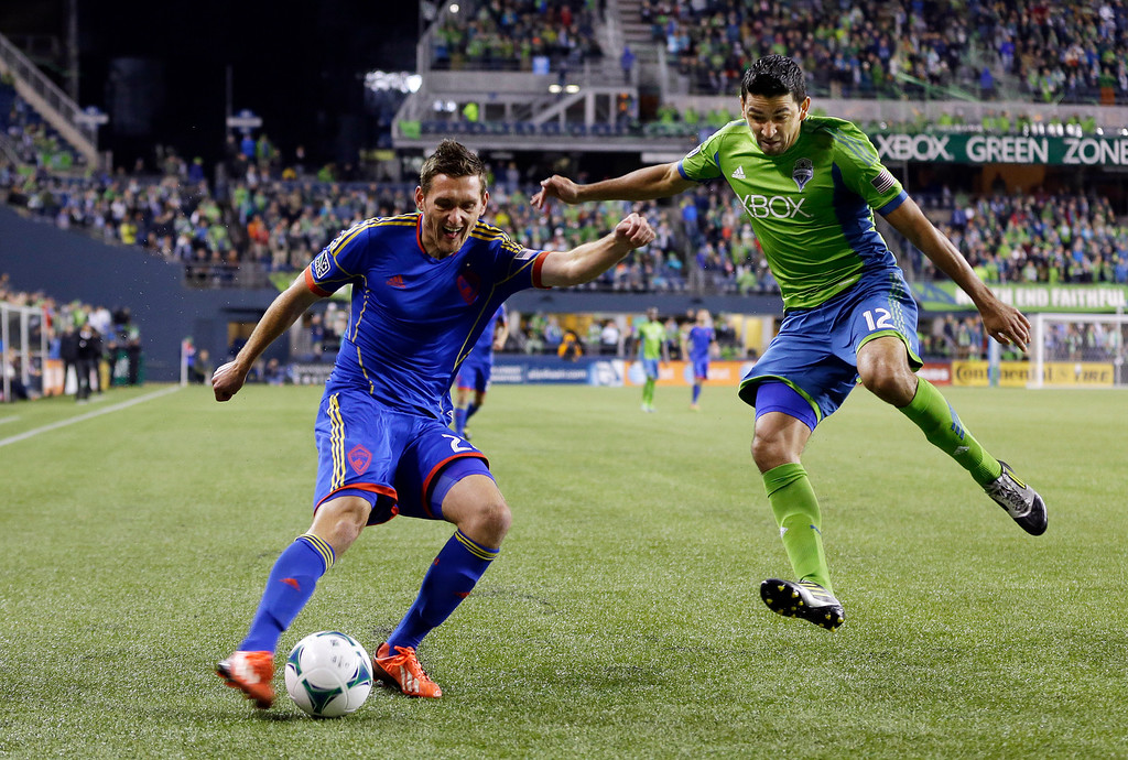 . Colorado Rapids\' Shane O\'Neill, left, crosses the ball around the defense of Seattle Sounders\' Leo Gonzalez, right, in the first half of a knockout-round match in the MLS Cup soccer playoffs Wednesday, Oct. 30, 2013, in Seattle. (AP Photo/Ted S. Warren)