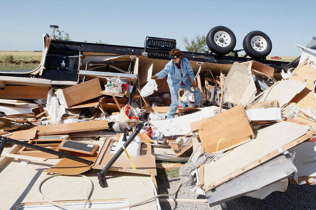 . Mikie Hooper of Tuttle, Oklahoma, collects her belongings from her RV which was destroyed by a tornado in El Reno, Oklahoma, June 1, 2013. Mikie and her husband Paul were attending the Oklahoma State Trap Shoot Competition but fled home to Tuttle to escape the storm. Nine people were killed in tornadoes that swept through central Oklahoma on Friday, part of a storm system that caused widespread flooding in Oklahoma City and its suburbs, the state\'s chief medical examiner said on Saturday. REUTERS/Bill Waugh
