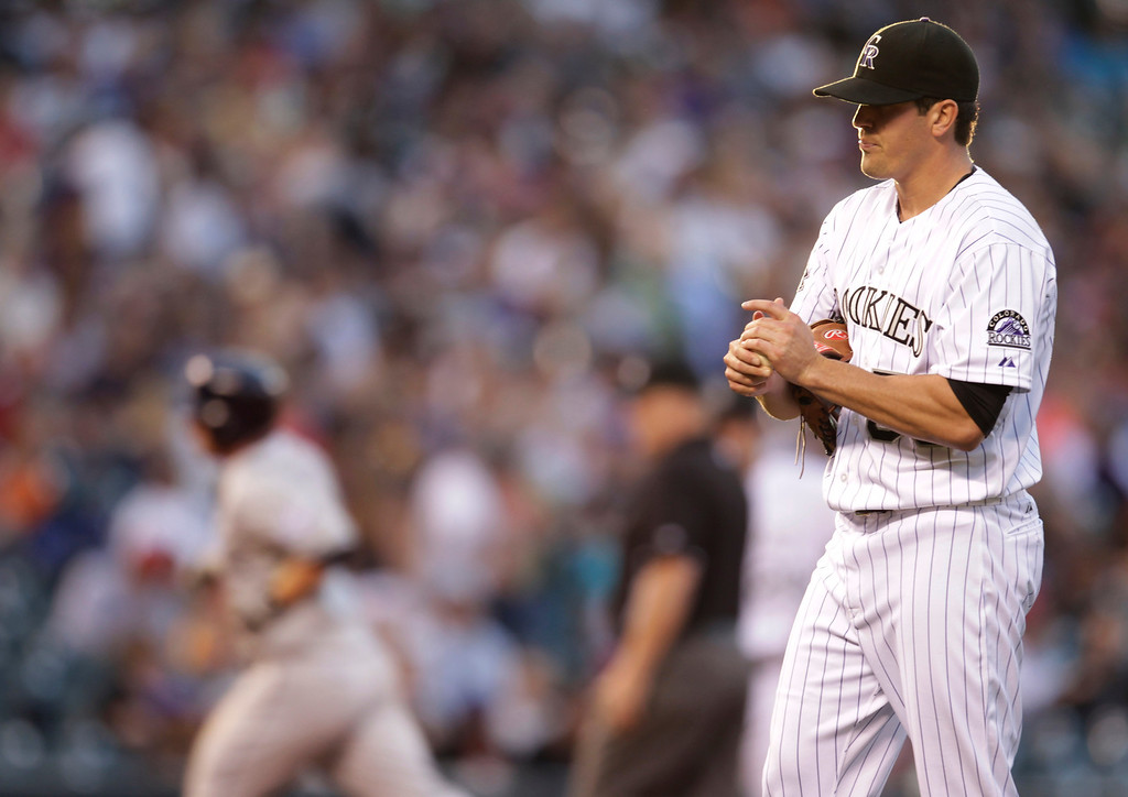 . Colorado Rockies starting pitcher Jeff Manship, right, rubs the baseball as San Diego Padres\' Jedd Gyorko rounds the bases after his solo home run in the third inning of a baseball game in Denver on Tuesday, Aug. 13, 2013.(AP Photo/Joe Mahoney)