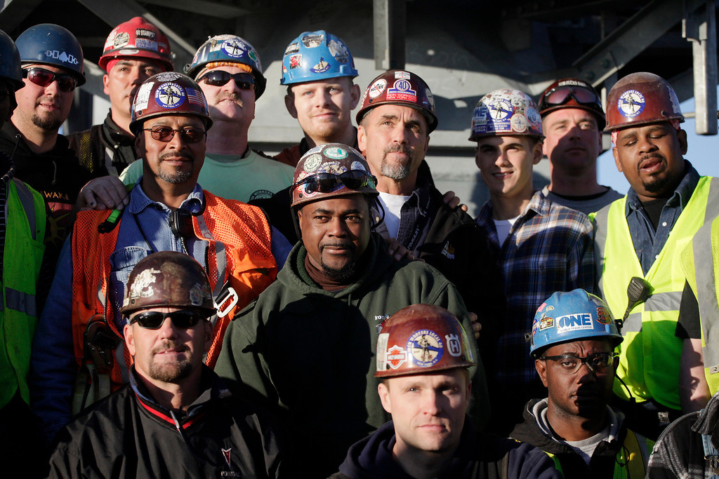 . Iron workers pose for photos on the roof of One World Trade center before the final piece of spire is hoisted in place, Friday, May 10, 2013 in New York. The addition of the spire, and its raising of the buildingís height to 1,776 feet, would make One World Trade Center the tallest structure in the U.S. and third-tallest in the world. (AP photo/Mark Lennihan)