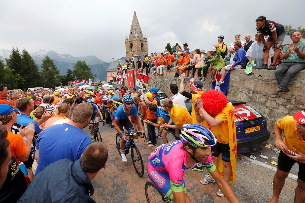 . The pack of riders makes his way among spectators as he climbs the Alpe d\'Huez mountain during the 172.5km eighteenth stage of the centenary Tour de France cycling race from Gap to l\'Alpe d\'Huez, in the French Alps, July 18, 2013.           REUTERS/Jean-Paul Pelissier