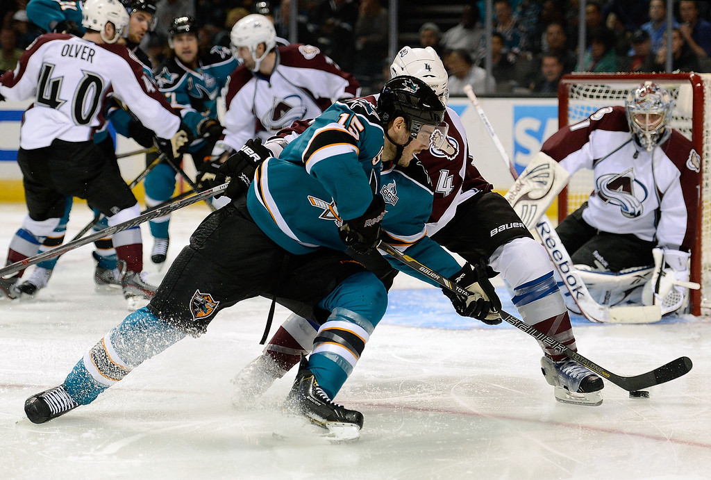 . James Sheppard #15 of the San Jose Sharks gets an assist passing the puck by Greg Zanon #4 of the Colorado Avalanche to teammate TJ Galiardi #21 who scored on the play in the second period at HP Pavilion on February 26, 2013 in San Jose, California.  (Photo by Thearon W. Henderson/Getty Images)