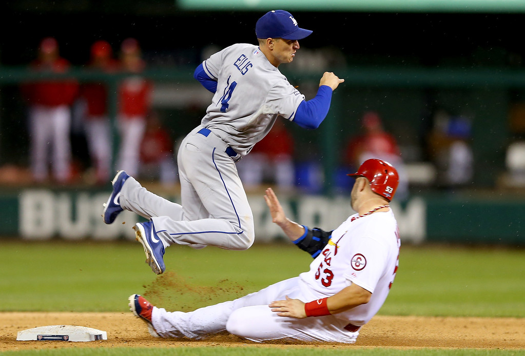 . ST LOUIS, MO - OCTOBER 18:  Mark Ellis #14 of the Los Angeles Dodgers turns a double play as Matt Adams #53 of the St. Louis Cardinals is out at second base in the sixth inning in Game Six of the National League Championship Series at Busch Stadium on October 18, 2013 in St Louis, Missouri.  (Photo by Elsa/Getty Images)