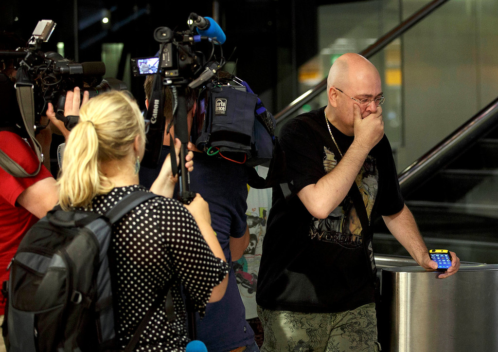 . A relative walks past members of the press as he arrives at Schiphol airport in Amsterdam, Thursday, July 17, 2014.  Ukraine said a passenger plane carrying 295 people was shot down Thursday as it flew over the country, and both the government and the pro-Russia separatists fighting in the region denied any responsibility for downing the plane. (AP Photo/Phil Nijhuis) (AP Photo/Phil Nijhuis)