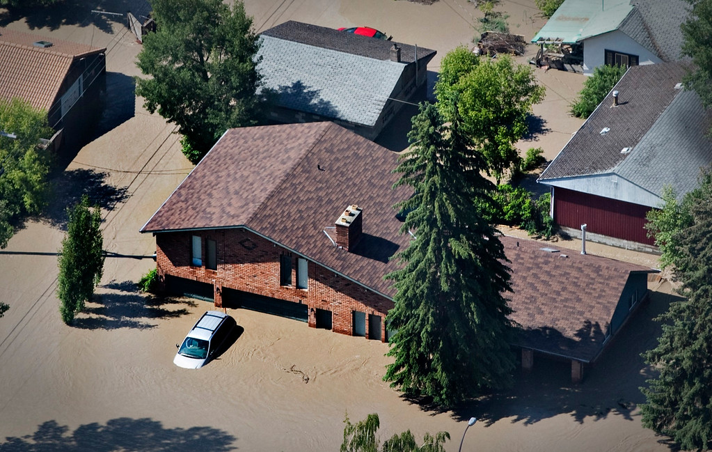 . A vehicle sits in the driveway of a house after the Bow River overflowed its banks into a residential area of Calgary, Alberta June 22, 2013.    REUTERS/Andy Clark