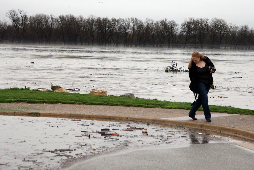 . Christine Waters gets a first hand look to take pictures of the flooding Mississippi River Thursday April 18, 2013 by the north boat ramp in Burlington, Iowa. The crest on the Mississippi River is predicted to reach 22.3 feet Sunday and would be the third highest on record.(AP Photo/The Hawk Eye, John Gaines)