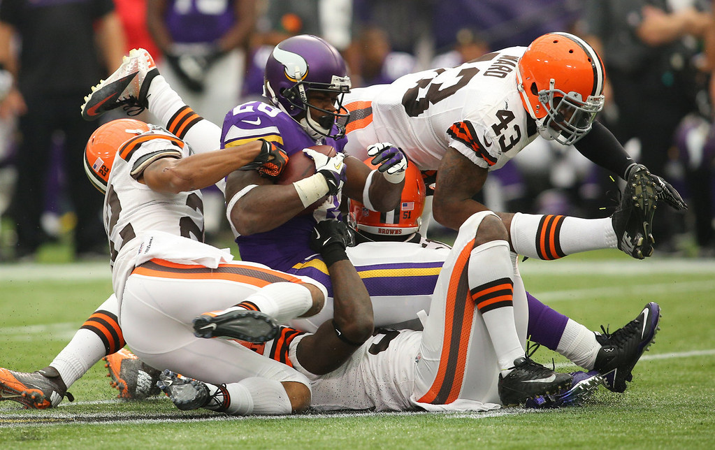 . Adrian Peterson #28 of the Minnesota Vikings gets tackled by Buster Skrine #22, Barkevious Mingo #51 and T.J. Ward #43 of the Cleveland Browns on September 22, 2013 at Mall of America Field at the Hubert Humphrey Metrodome in Minneapolis, Minnesota. (Photo by Adam Bettcher/Getty Images)