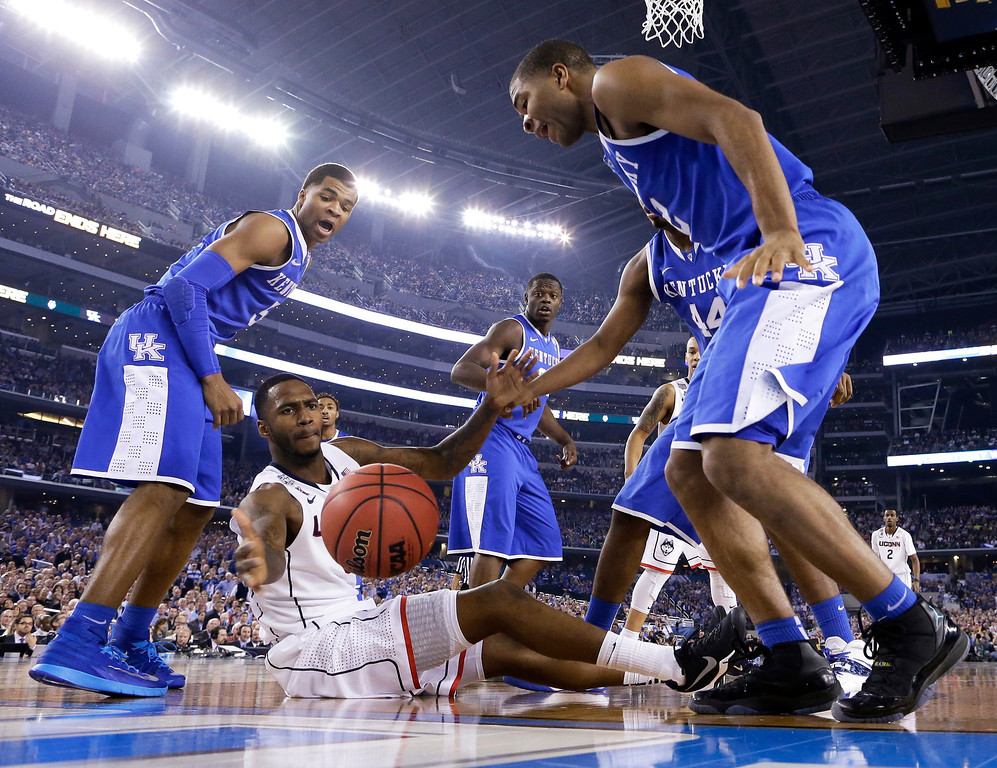 . Connecticut forward Phillip Nolan, center, loses the ball between Kentucky\'s Andrew Harrison, left, and Aaron Harrison, right, during the second half of the NCAA Final Four tournament college basketball championship game Monday, April 7, 2014, in Arlington, Texas. (AP Photo/Eric Gay)