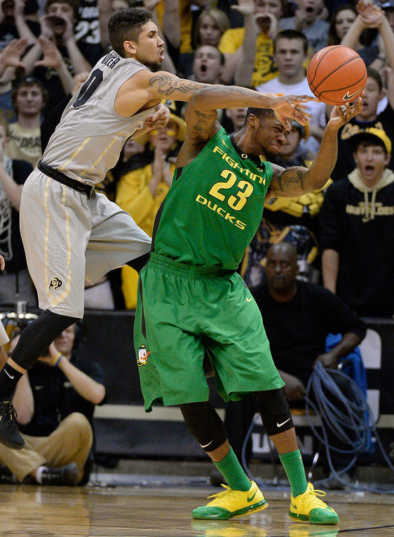. Oregon Ducks forward Elgin Cook (23) gets fouled by CU guard Askia Booker (0) late in the sec on half January 5, 2014 at Coors Events Center. Colorado Buffaloes defeated the Oregon Ducks 100-91. (Photo by John Leyba/The Denver Post)