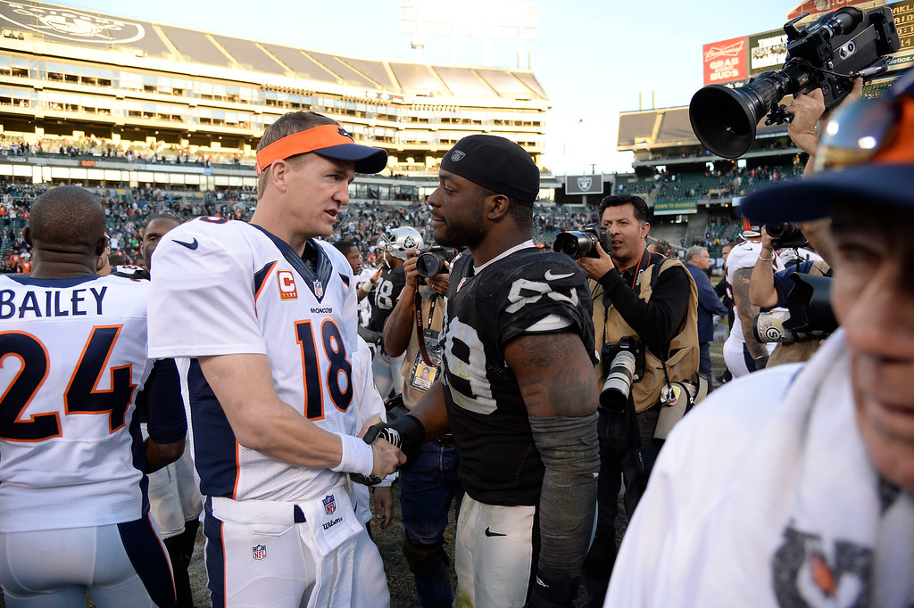 . Denver Broncos quarterback Peyton Manning (18) shakes hands with Oakland Raiders defensive end Lamarr Houston (99) after the game at O.co Coliseum. (Photo by John Leyba/The Denver Post)