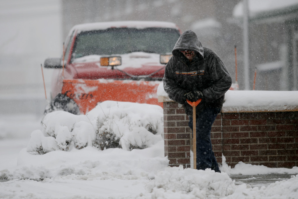 . DENVER, CO. - MARCH 23: Rene Acosta sweeps snow from the sidewalk near the corner of Broadway and 6th Ave. in Denver. Heavy snow continues to fall Denver area. Denver, Colorado. March 23, 2013. (Photo By Hyoung Chang/The Denver Post)