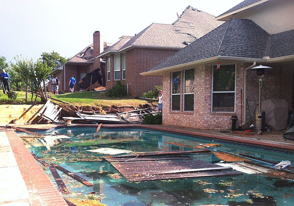 . People survey damage from a tornado that hit Edmond, Okla., on Sunday, May 19, 2013. A powerful storm system rumbled through the Plains and upper Midwest on Sunday, spawning tornadoes that damaged roofs and structures near Oklahoma City and kicked up debris in Wichita, Kan. (AP Photo/Sean Murphy)