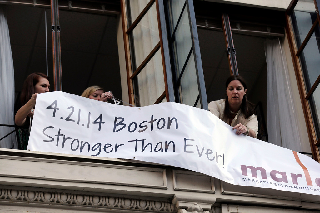 . Marla Fogelman, right,  hangs a banner on the second floor over Marathon Sports store, the site of the first bomb blast in 2013, before the start of the 118th Boston Marathon Monday, April 21, 2014 in Boston. (AP Photo/Charles Krupa)