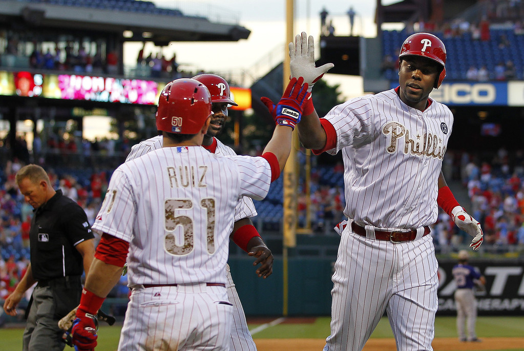 . PHILADELPHIA, PA - MAY 26: John Mayberry Jr. #15 of the Philadelphia Phillies is congratulated by teammate Carlos Ruiz #51 after he hit a two run home run in the seventh inning scoring Ryan Howard #6 against the Colorado Rockies during a game at Citizens Bank Park on May 26, 2014 in Philadelphia, Pennsylvania.The Phillies defeated the Rockies 9-0. (Photo by Rich Schultz/Getty Images)