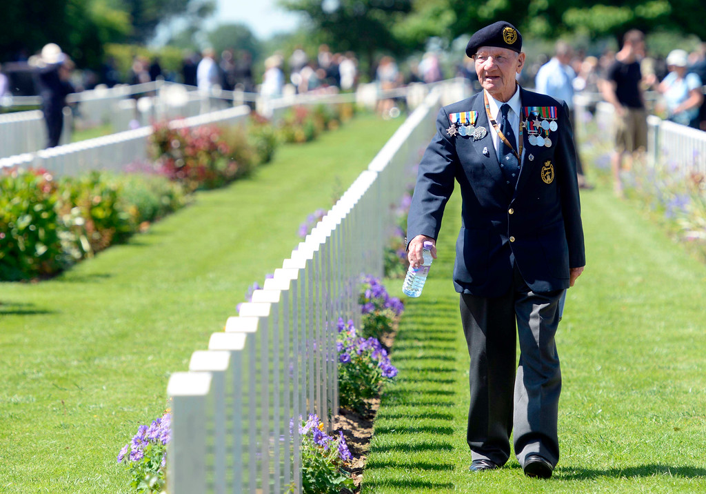 . A British veteran walks among headstones before participating in a French-British D-Day commemoration ceremony at the British War Cemetery in Bayeux, France, Friday, June 6, 2014. World leaders and veterans gathered by the beaches of Normandy on Friday to mark the 70th anniversary of World War Two\'s D-Day landings. (AP Photo/Thomas Bregardis, Pool)