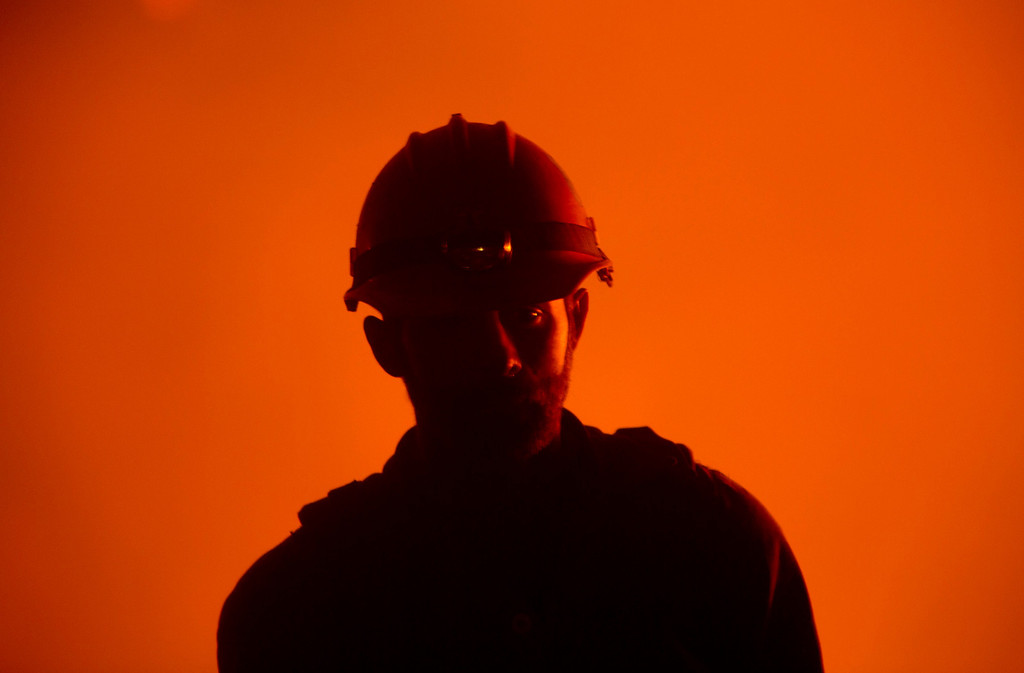 . Idaho City Hotshots firefighter Chance Harrington, from Boise is lit from the fires from a back burn near Pine, Idaho while fighting the Elk fire Wednesday Aug. 14, 2013. The Elk fire has burned 111,977 acres and was 10% contained as of 8am.  (AP Photo/Idaho Statesman, Kyle Green)