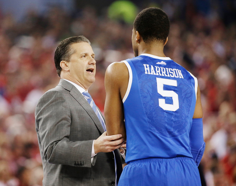 . Kentucky head coach John Calipari talks with guard Andrew Harrison (5) during the first half of the NCAA Final Four tournament college basketball semifinal game against Wisconsin Saturday, April 5, 2014, in Arlington, Texas. (AP Photo/David J. Phillip)
