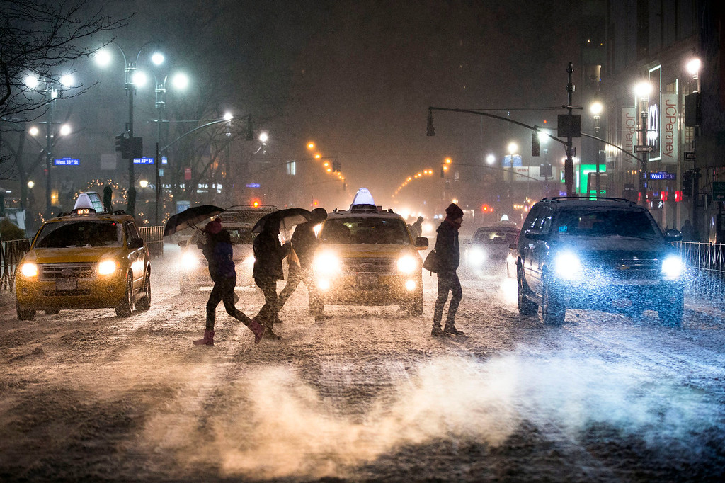. Pedestrians cross 34th Street and 6th Avenue under falling snow in Herald Square, Thursday, Jan. 2, 2014, in New York. The storm is expected to bring snow, stiff winds and punishing cold into the Northeast. (AP Photo/John Minchillo)