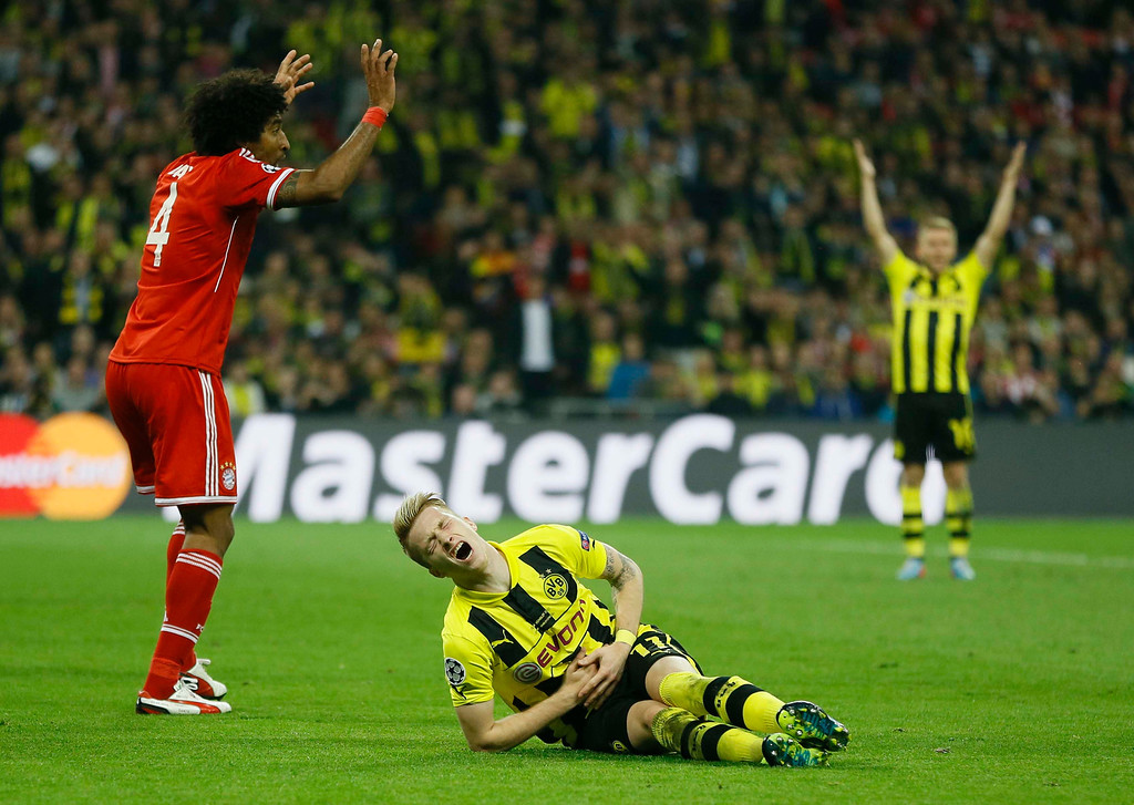 . Bayern\'s Dante of Brazil, left, fouls Dortmund\'s Marco Reus, leading to a penalty,  during the Champions League Final soccer match between Borussia Dortmund and Bayern Munich at Wembley Stadium in London, Saturday May 25, 2013. (AP Photo/Kirsty Wigglesworth)