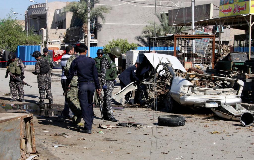 . Iraqi policemen examine remains of a car bomb in Baghdad\'s Sadr City March 19, 2013.  REUTERS/Qahtan al-Sudani