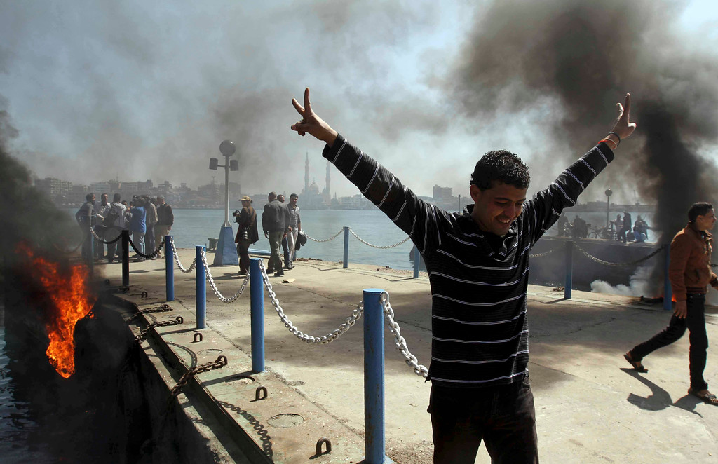 . An Egyptian flashes the victory sign after several protesters set fire to tires on the city\'s dock in an attempt to prevent ships from coming in to the strategic city of Port Said at the Mediterranean end of the Suez Canal, in Egypt, Saturday, March 9, 2013.(AP Photo/Ahmed Ramadan)