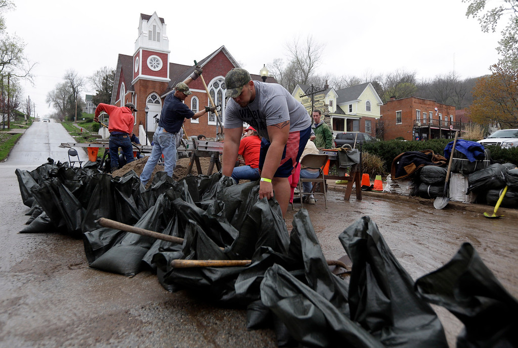 . Steve Dieckhaus arranges sand bags being filled in hopes of holding back the rising Mississippi River Thursday, April 18, 2013, in Clarksville, Mo.  (AP Photo/Jeff Roberson)