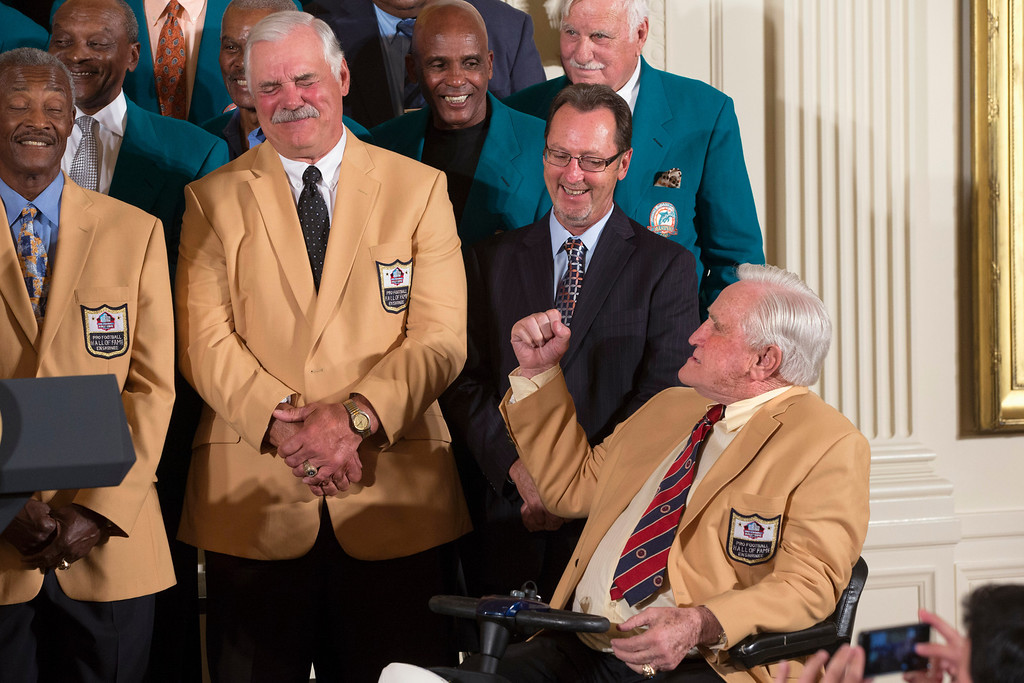. Former Miami Dolphins fullback Larry Csonka, second from left, grimaces as Hall of Fame coach Don Shula jokingly shakes a fist at him, during a ceremony in the East Room of the White House in Washington, Tuesday, Aug. 20, 2013, where President Barack Obama honored the Super Bowl VII football Champion Miami Dolphins. The 1972 Miami Dolphins remain the only undefeated team in NFL history. Wide receiver Paul Warfield is at left. (AP Photo/Jacquelyn Martin)